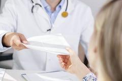 De arts geeft een document aan patiënt Stock Fotografie