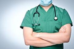 De arts in groen schrobt gevouwen zijn wapens over zijn borst Stock Fotografie