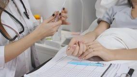 De arts in het ziekenhuis gaat een injectie aan de patiënt geven De arts pakt een beschikbare spuit uit stock videobeelden