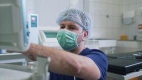 De arts in het ziekenhuis kleedde zich in steriele kleding en het maskerwerk met kenmerkend materiaal Ultrasone klankonderzoek stock videobeelden