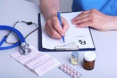 De arts houdt een blaar met pillen in zijn hand en schrijft het voorschrift in het werkplaatsclose-up uit prescribe stock afbeeldingen
