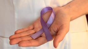 De arts houdt een purper lint als symbool van de dag dichte omhooggaand van de epilepsievoorlichting stock video