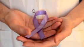 De arts houdt een purper lint als symbool van de dag dichte omhooggaand van de epilepsievoorlichting stock footage