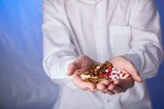 De arts houdt multi-colored pillen en pak verschillende tabletblaren in handen De panacee, het leven sparen de dienst, schrijft g stock afbeelding