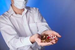 De arts houdt multi-colored pillen en pak verschillende tabletblaren in handen De panacee, het leven sparen de dienst, schrijft g royalty-vrije stock afbeeldingen