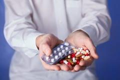 De arts houdt multi-colored pillen en pak verschillende tabletblaren in handen De panacee, het leven sparen de dienst, schrijft g stock fotografie