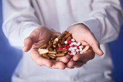 De arts houdt multi-colored pillen en pak verschillende tabletblaren in handen De panacee, het leven sparen de dienst, schrijft g royalty-vrije stock foto's