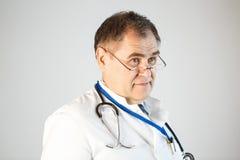 De arts kijkt vooruit, glazen op het uiteinde van zijn neus, opgeheven wenkbrauwen, een stethoscoop en een kenteken die van zijn  stock foto