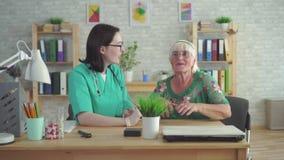 De arts in de kliniek helpt om een gehoorapparaat in het oor van bejaarde te zetten stock footage