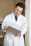 De arts leest de Grafiek van Patiënten stock afbeeldingen