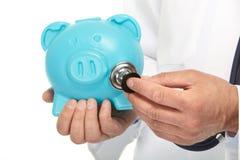 De arts luistert aan het spaarvarken Stock Afbeelding