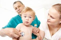 De arts luistert babyboy met stethoscoop. Stock Afbeeldingen