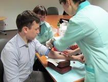De arts maakt de patiënt tot een injectie in een ader royalty-vrije stock afbeelding