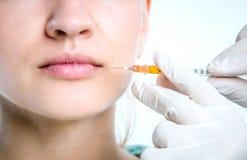 De arts maakt een injectie in de lippen van een patiënt Stock Afbeelding