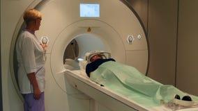 De arts maakt hersenentomografie voor een vrouw op MRI-aftasten stock footage