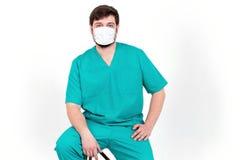 De arts in masker toont emotie Op de witte achtergrond Stock Foto's