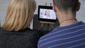 De arts meldt de resultaten van het algemeen medische onderzoek door videopraatje met een echtpaar online geneeskunde stock video