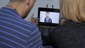 De arts meldt de resultaten van het algemeen medische onderzoek door videopraatje met een echtpaar online geneeskunde stock videobeelden