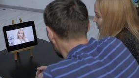 De arts meldt de resultaten van het algemeen medische onderzoek door videopraatje met een echtpaar online geneeskunde stock footage