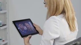 De arts meldt de resultaten van het algemeen medische onderzoek door videopraatje met een echtpaar online geneeskunde 4K stock videobeelden