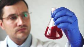 De arts mengt de rode vloeistof in de flesnadruk op buis stock footage