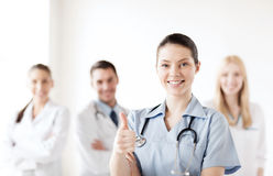 De arts met groep dokters het tonen beduimelt omhoog Stock Foto