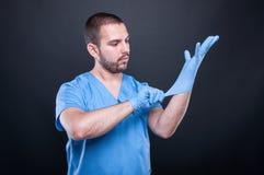 De arts met schrobt het zetten op zijn latexhandschoenen Stock Foto