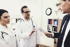 De arts met stethoscoop weigert om geld van patiënt te nemen Concept corruptie in geneeskunde stock afbeelding