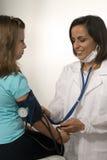 De arts neemt de Bloeddruk van het Meisje. Verticaal Stock Afbeeldingen