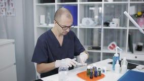 De arts-onderzoeker in rubberhandschoenen bestudeert genetisch gemodificeerde micro-organismen De arts bekijkt binnen reagentia stock footage