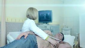 De arts onderzoekt een geduldig hart van ` s met ultrasone klank Diagnostiek en Ultrasone klankonderzoek van de patiënt stock footage
