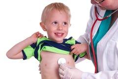 De arts onderzoekt een jong kind stock foto