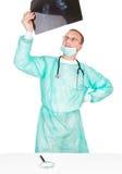 De arts onderzoekt een röntgenstraal met een vergrootglas. CLO Stock Afbeeldingen