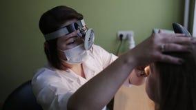 De arts onderzoekt een vrouwelijke patiënt in kliniek stock videobeelden