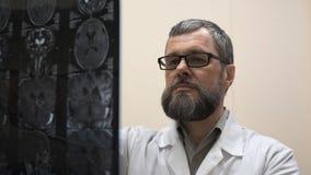 De arts onderzoekt MRI van de hersenen van de patiënt stock videobeelden