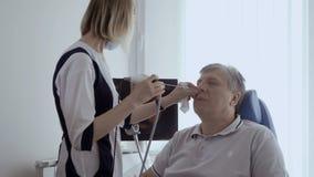 De arts onderzoekt neus van de oude mens met ent telescoop stock footage