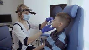 De arts onderzoekt neus van weinig jongen met oorspiegel stock video