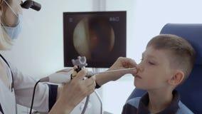 De arts onderzoekt neus van weinig Kaukasische jongen met ENT telescoop stock footage