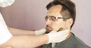 De arts onderzoekt de patiënt in de kliniek stock video