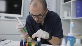 De arts onderzoekt reagentia in het laboratorium De laboratoriummedewerker leidt laboratoriumonderzoeken stock footage