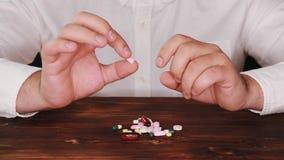 De arts plukt een pil van een stapel van verspreide degenen De verslaafde kiest een pil De tabletten zijn verspreid op de lijst stock video
