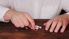De arts plukt een pil van een stapel van verspreide degenen De verslaafde kiest een pil De tabletten zijn verspreid op de lijst stock footage