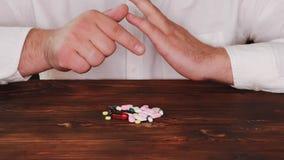 De arts plukt een pil van een stapel van verspreide degenen De verslaafde kiest een pil De tabletten zijn verspreid op de lijst stock videobeelden