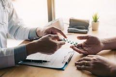 De arts richt aan drugtablet en introduceert de eigenschappen van de pijnstiller aan patiënt op kantoor royalty-vrije stock foto