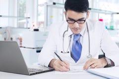 De arts schrijft geneeskunderecept in het laboratorium Stock Afbeeldingen