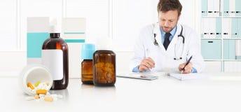 De arts schrijft voorschriftzitting op het bureaukantoor met voor pillen, drugs en geneeskundeflessen, medische behandelingconcep stock afbeelding