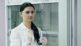 De arts schrijft wetenschappelijk experiment op de raad stock videobeelden
