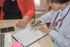 De arts spreekt met vrouwelijke patiënt en maakt nota's terwijl zit Royalty-vrije Stock Fotografie
