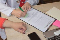 De arts spreekt met vrouwelijke patiënt en maakt nota's terwijl zit Stock Fotografie