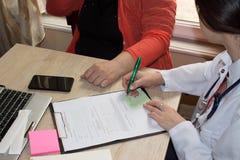 De arts spreekt met vrouwelijke patiënt en maakt nota's terwijl zit Royalty-vrije Stock Foto's